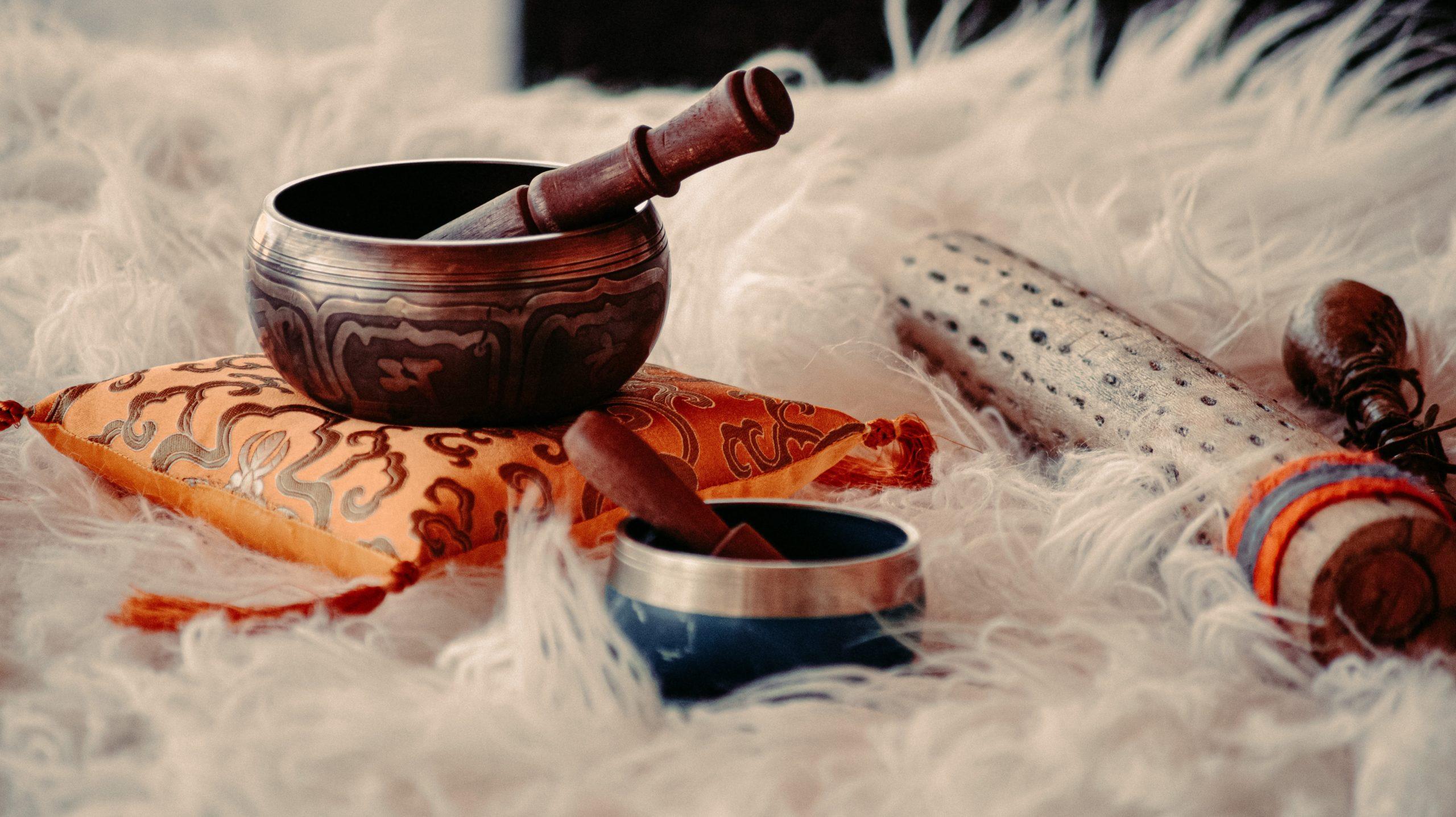 Tibetan singing bowls resting on a sheepskin rug