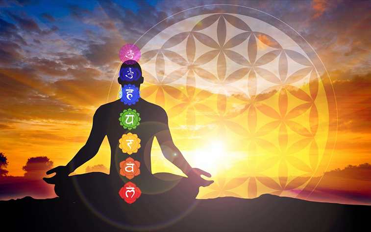 A silhouette of a man sitting in lotus pose with the chakra symbols placed on his body against a beautiful sunset