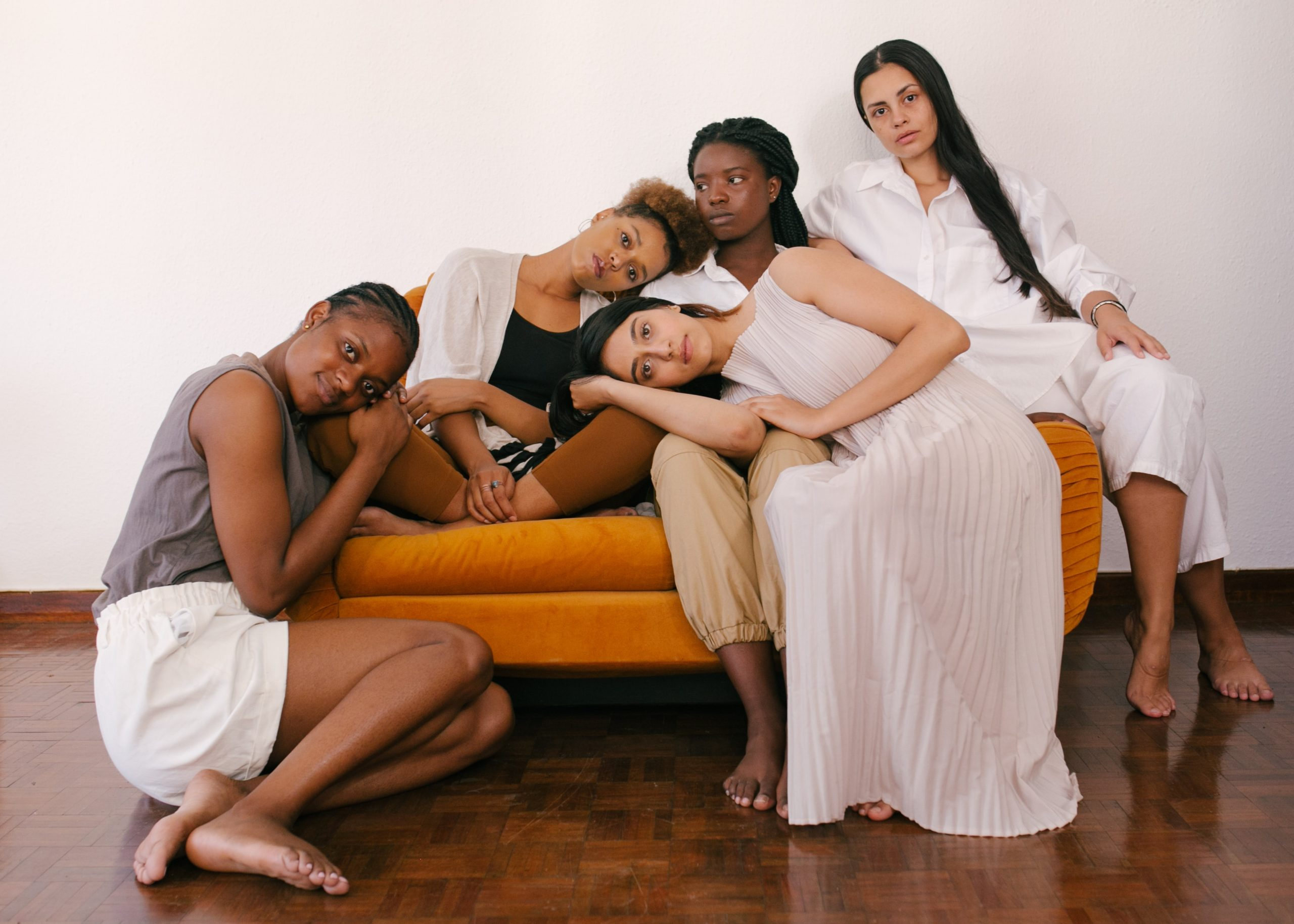 A group of five multiethnic women lounging on a couch
