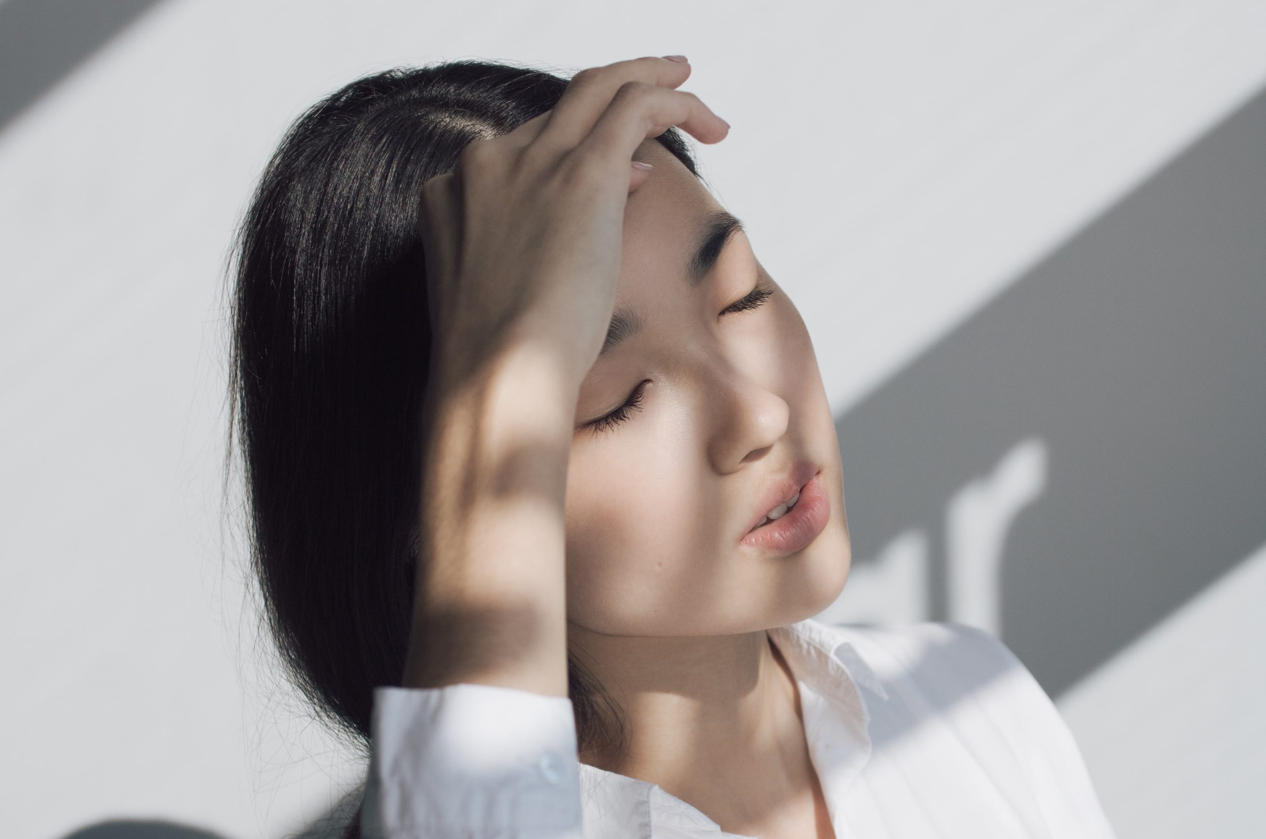 A Korean girl in a white shirt with her eyes closed and her hand by her forehead