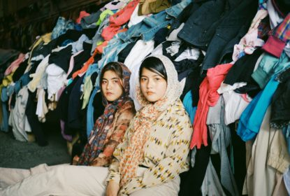 Two Asian Women Sitting in Front of Heaps of Clothing