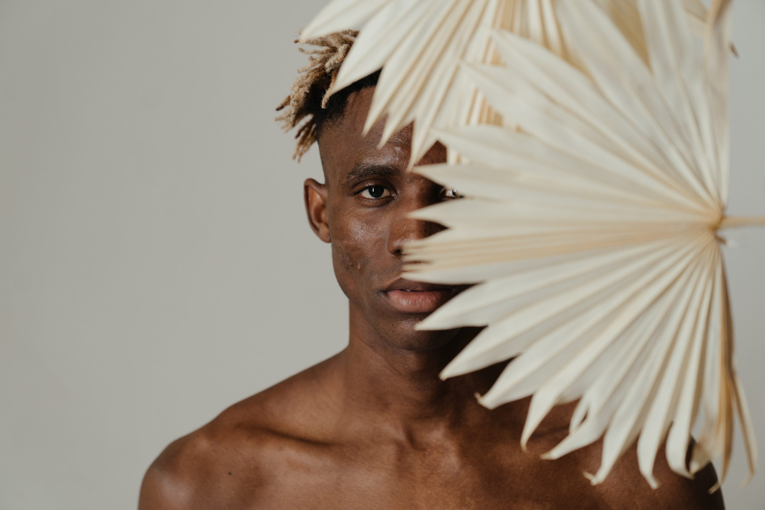 A man with acne holding a white palm frond in front of his face