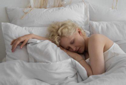 A woman sleeping on a softy, cushy bed