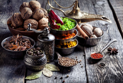 A picture of Indian herbs, nuts and an oil urn