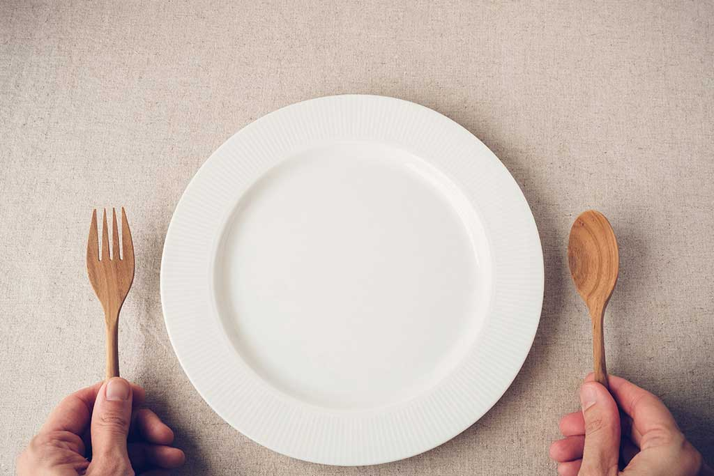 An empty plate and person's hands holding a wooden fork and spoon