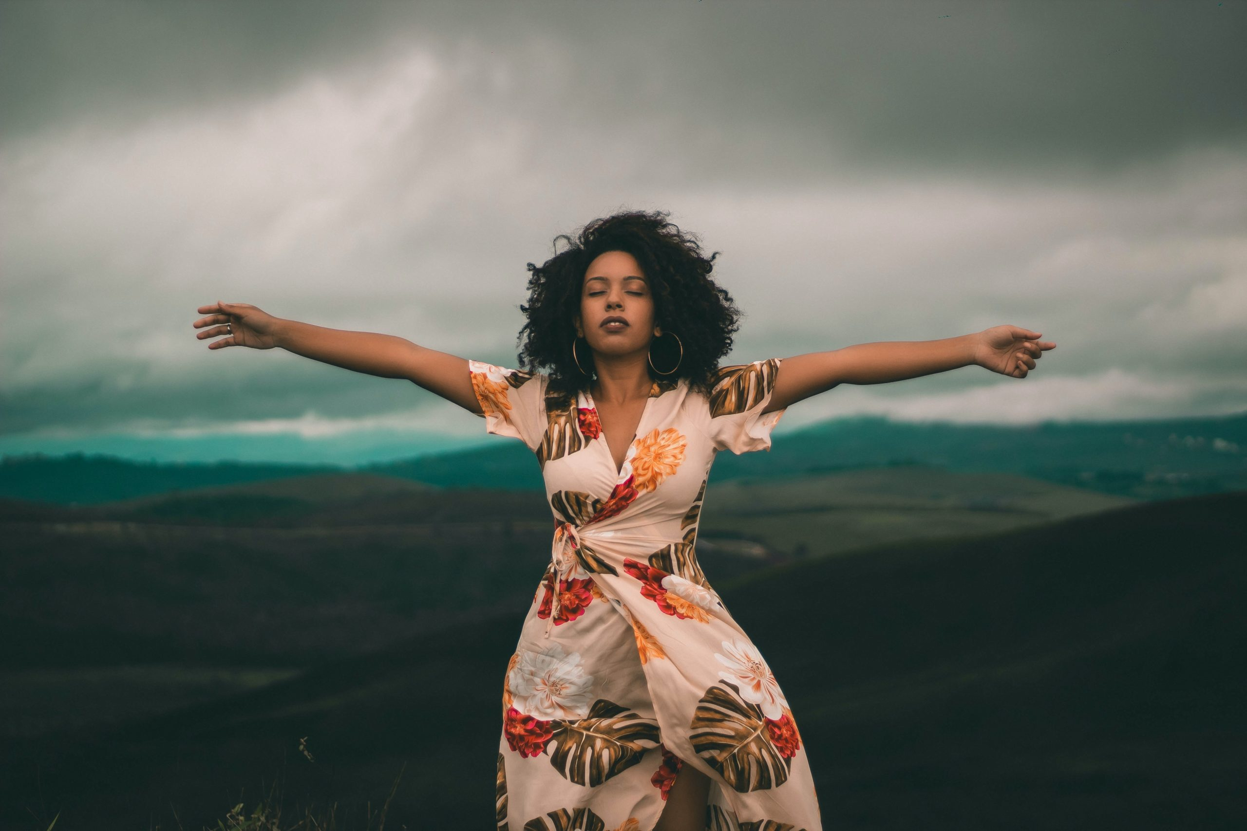 A black woman with glorious hair, arms spread in freedom